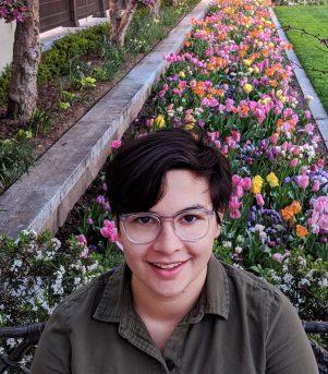 Photo of 2019-20 AAUW International Fellow Paula Florez-Salcedo in front of a flower bed.