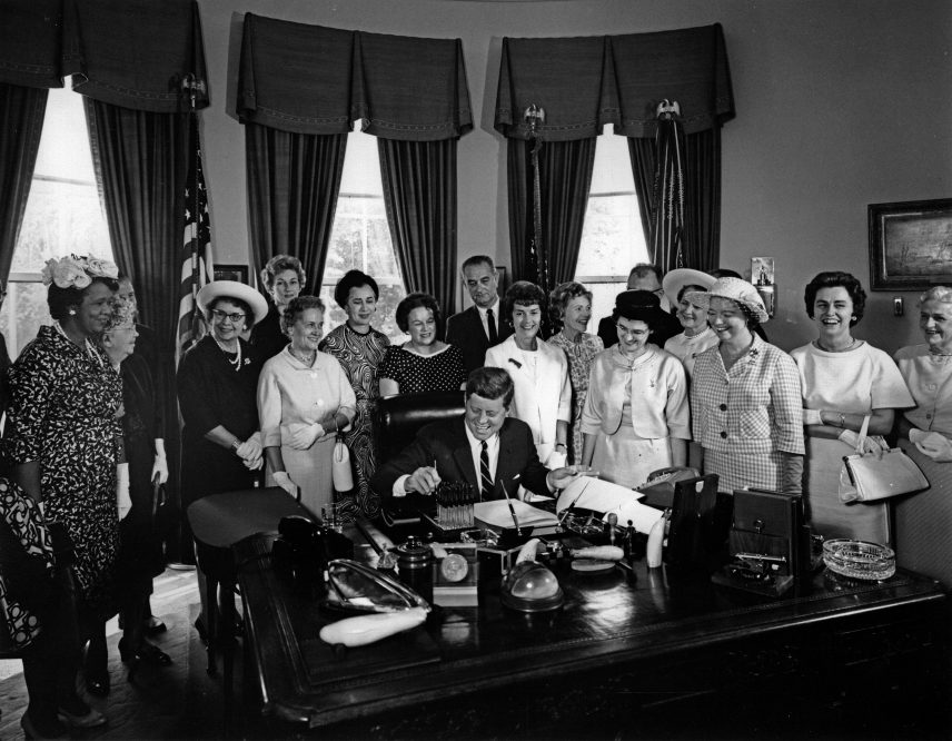 photo from 1964 of president John Kennedy signing the Equal Pay act. He is surrounded by Equal pay advocate, including AAUW members.