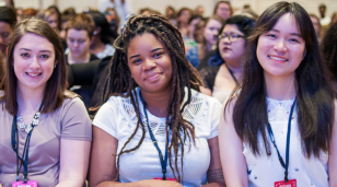 three students attending NCCWSL waiting for the next speaker to start.
