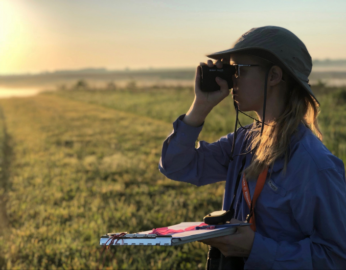 2018-19 American Fellow Jaime Coon looking through a lens at the horizon.