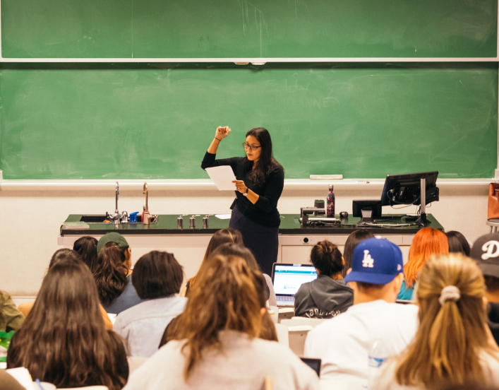 Woman teaches at chalkboard in front of lecture hall of students.