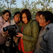 Photo of 2011-12 International Project Grantee Diedie Weng examining a camera with several young girls.