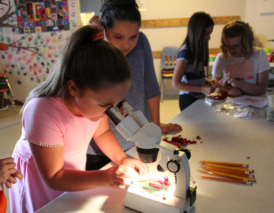 A young girl looks through microscope surrounded by classmates.