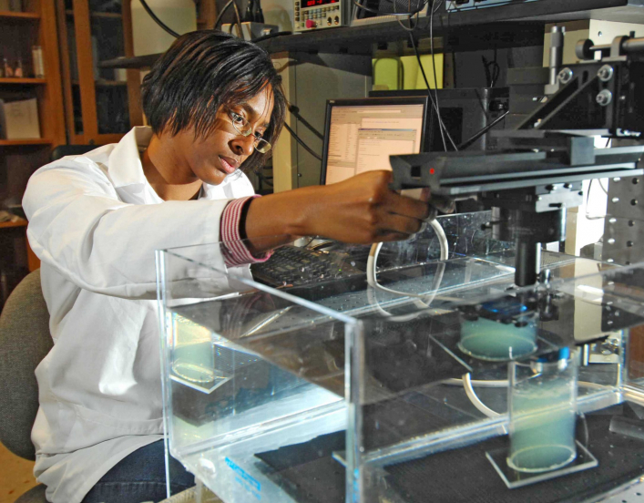 Woman in lab coat conducting research with lab equipment.