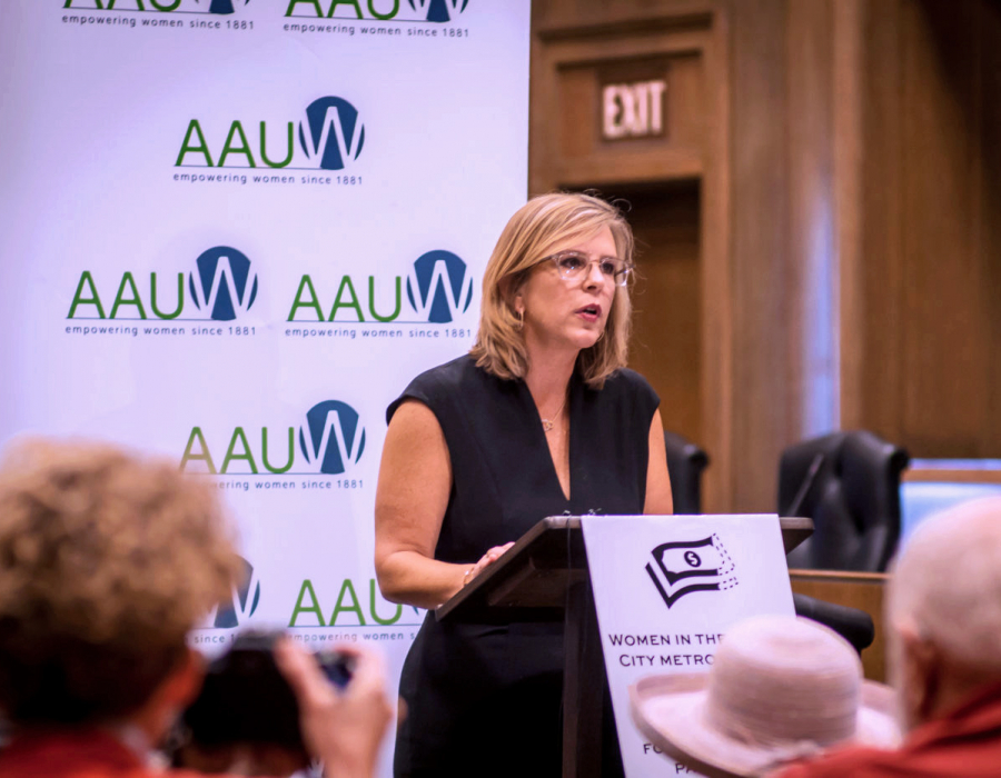 AAUW CEO Kim Churches stands at a podium speaking at press conference.