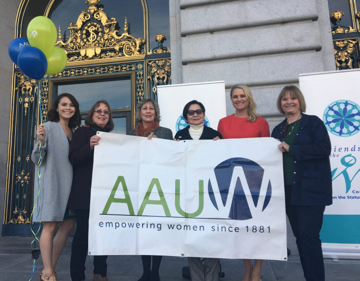 AAUW members holding a sign