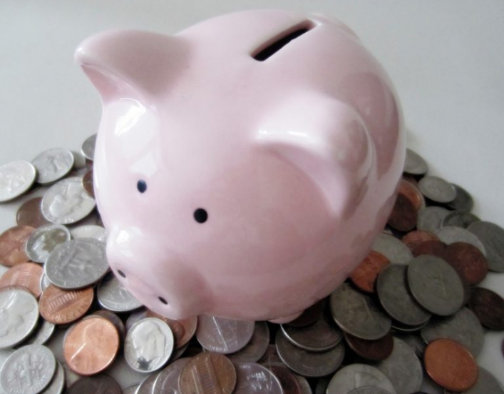 A piggy bank on a pile of coins, signifying a pay day