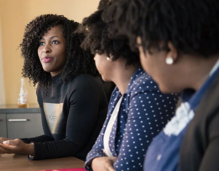 Women listening to another women at conference table