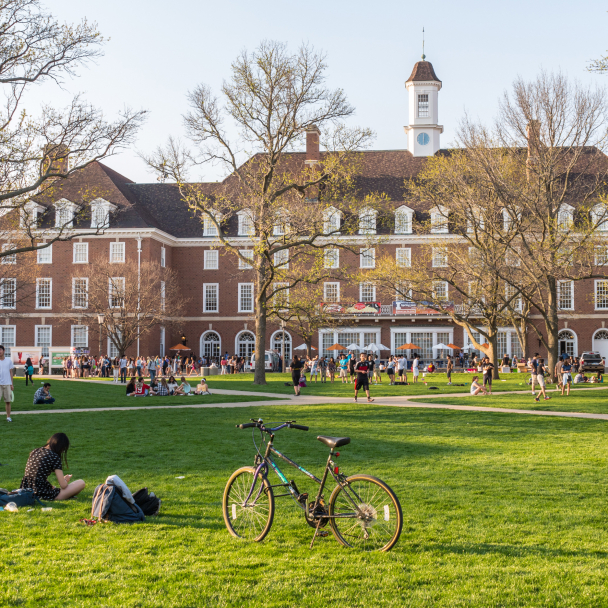 College students study and socialize on grassy area in front of campus building.