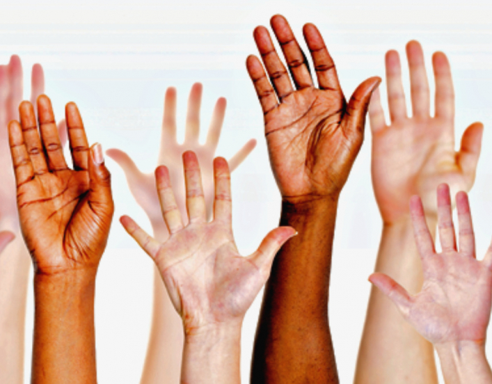 a group of raised hands in a vareity of skin hues
