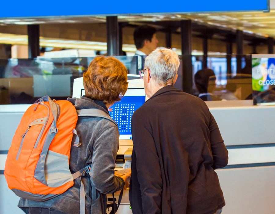 Two women check into their flight using an airport kiosk