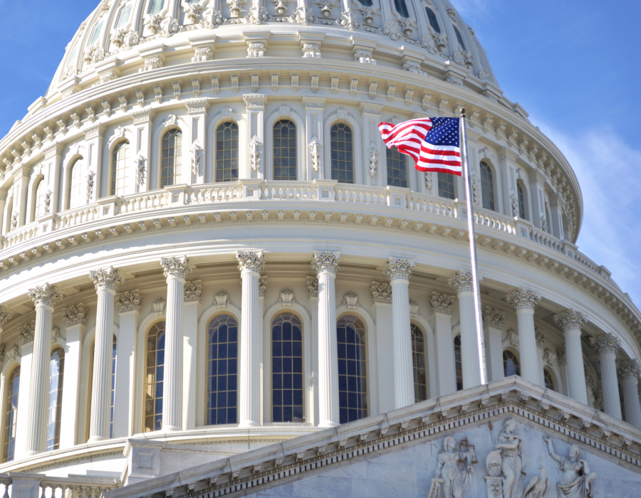 The dome of Capitol Building, Washington DC, and the American flag against a blue sky.