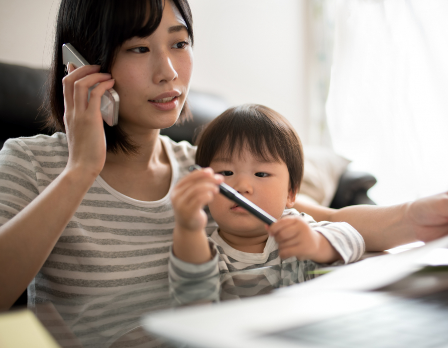 Woman in front of a laptop with her son on her lap