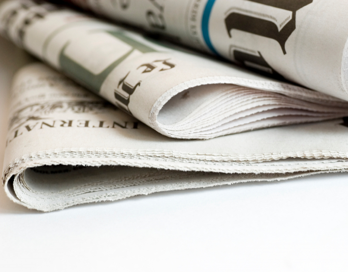 Newspapers folded and piled on top of each other.