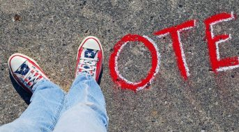 Feet make the shape of the letter 'V' and the word vote is spelled out in caulk