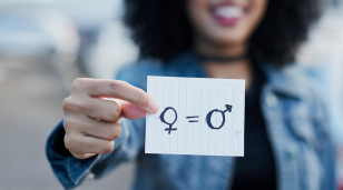 Out of focus woman holding a piece of paper with gender symbols and equals sign drawn on it.