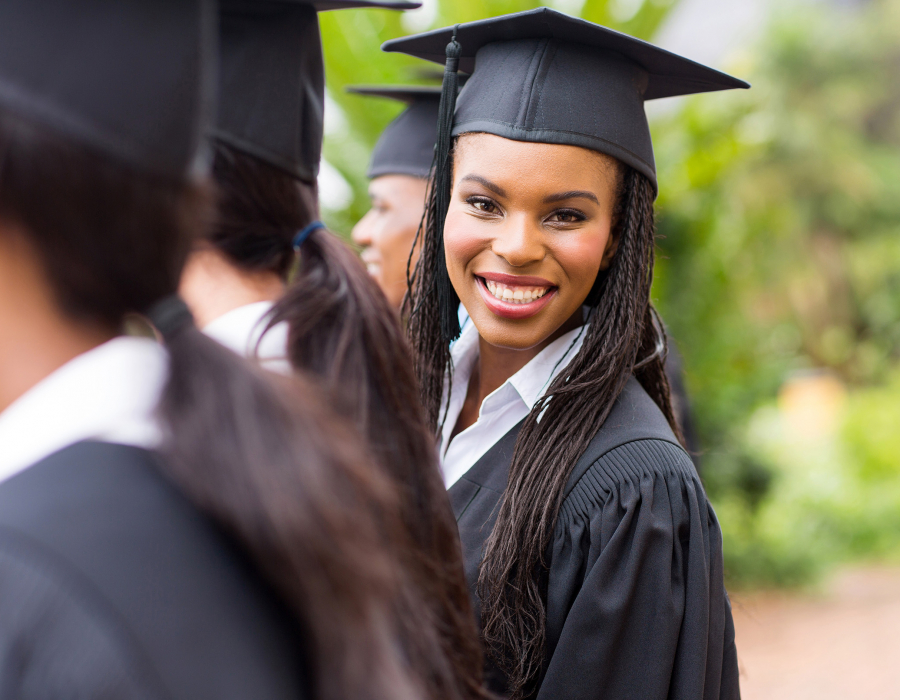 Young Black woman college graduate leans out of line to smile at camera in cap in gown.