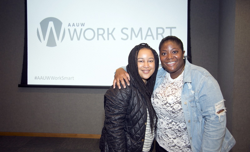 Two young Black women pose smiling with arms around each other in front of an AAUW Work Smart sign.