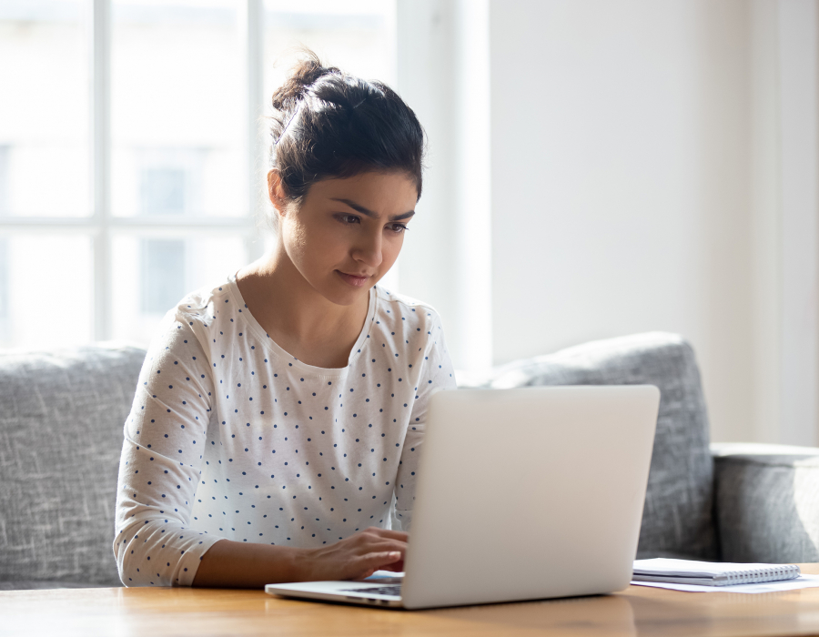 Focused young woman using laptop at home.