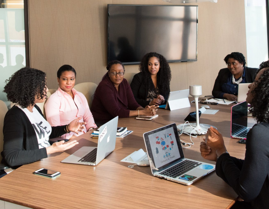 Black women around a conference table in an office, courtesy of Christina @ wocintechchat.com for Unsplash