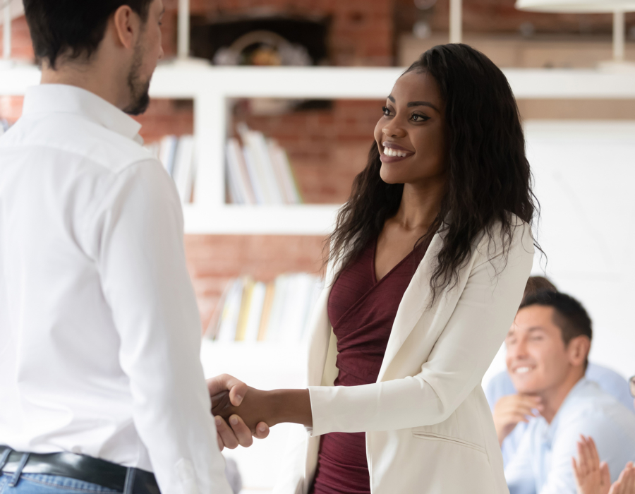 Young professional woman shakes hands with man, accepting job offer.