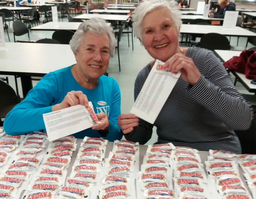 AAUW Appleton members Conney Polley and Rachel Edwards De Moss handing out a thousand Payday candy bars on an Equal Pay Day event on March 2019