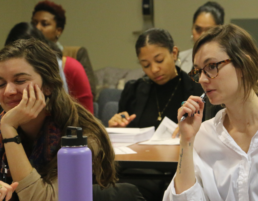 Two rows of female students attending a workshop in Washington DC. They are taking watching the presenter and taking notes.