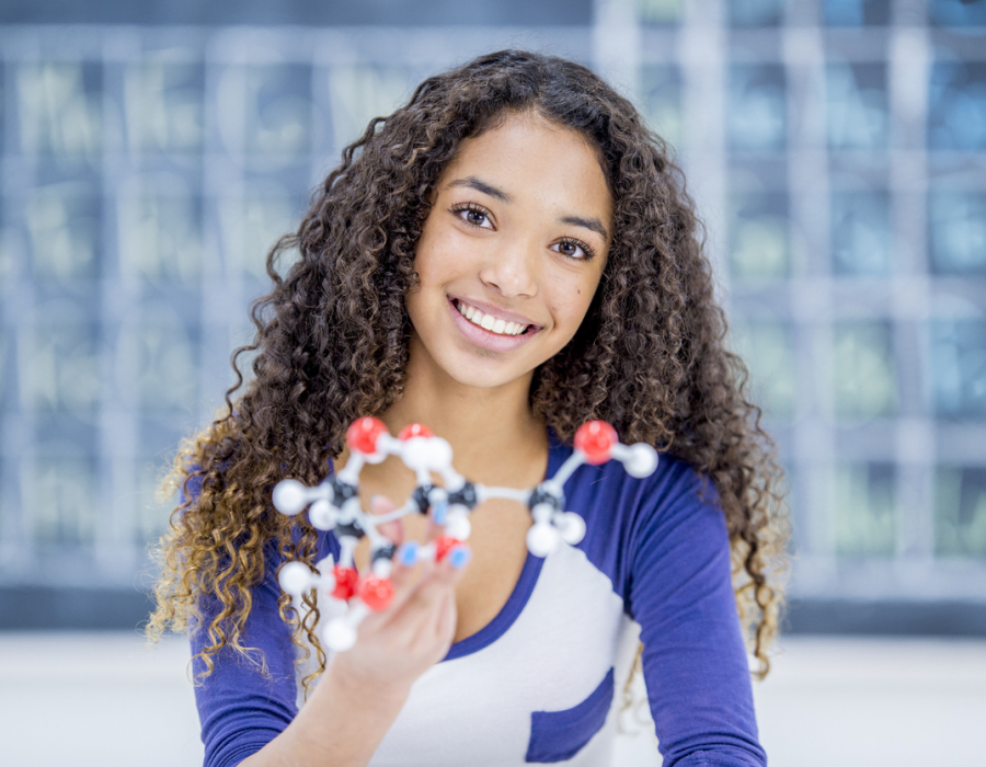 Smiling high school girl holding a model to illustrate STEM fields
