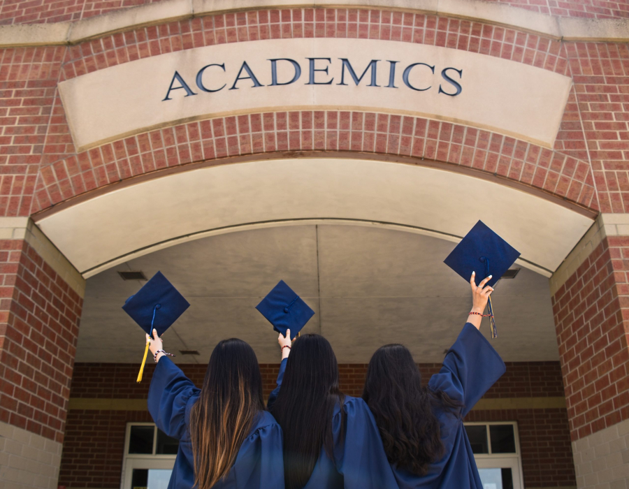 Three women with graduation gowns holding their caps in the air
