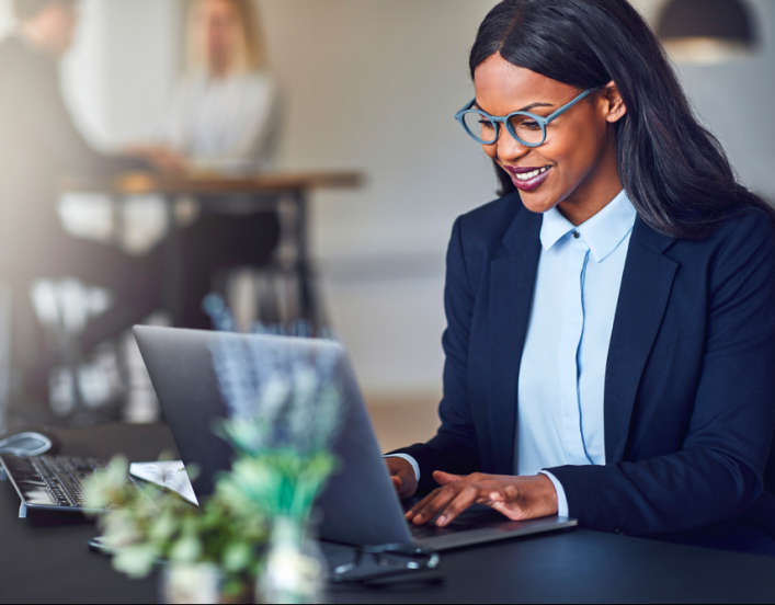 Smiling black woman in a suit on a laptop at a desk
