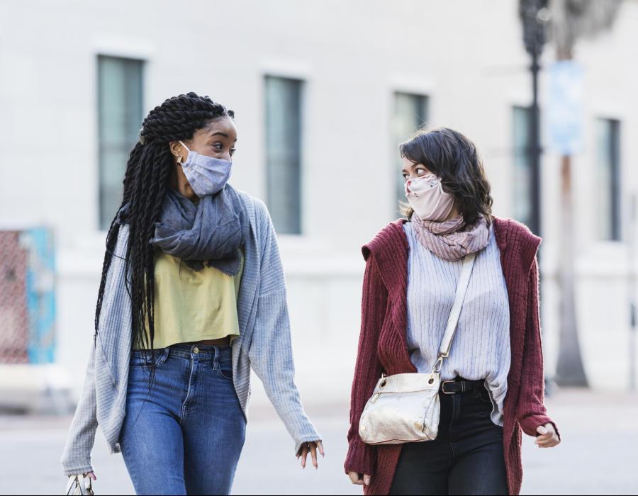 Two multi-ethnic young women in their 20s walking across a city street. They are side by side, looking at each other, conversing. They are wearing protective face masks, trying to prevent the spread of coronavirus during the COVID-19 pandemic.