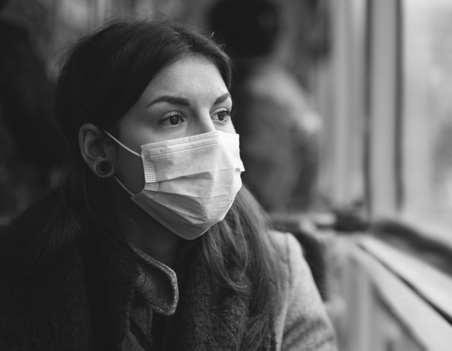 Black and white photo of a latina woman looking out a window wearing a surgical mask.