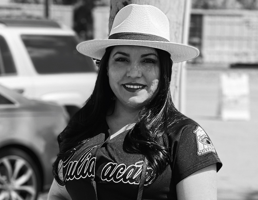 Black and white photo of a smiling latina woman in casual clothes.