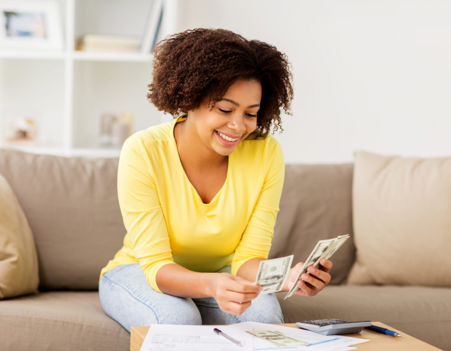 Woman sitting on sofa looking at spreadsheet and calculator