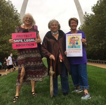Photo of AAUW members standing in front of the Gateway Arch in St. Louis, MO holding signs.