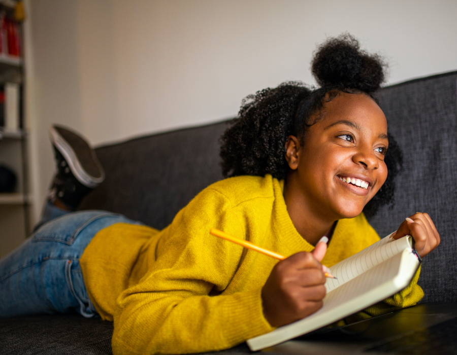 Teenager girl on sofa with notebook